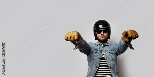 Young biker in a blue denim jacket pretending to ride a motorcycle isolated on white background Wallpaper Mural