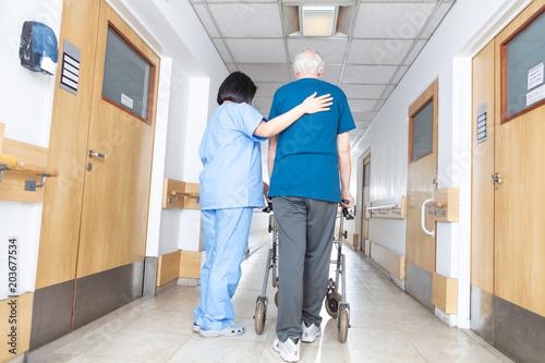 Photo  Asian nurse helping elder man walking in rehab facility