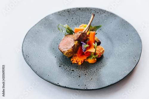 Modern French cuisine: Close up roasted Lamb neck & rack served with carrot, yellow curry served in black stone plate.