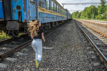 A Young Charming Girl Runs After The Railway Carriage Of A Departing Train