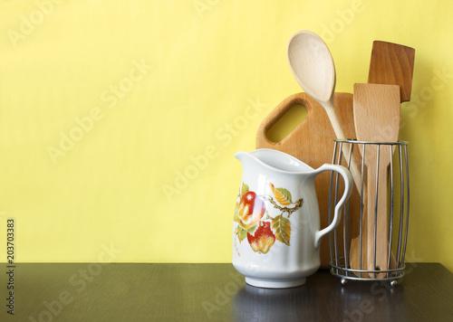 Kitchen utensils on dark shelf over yellow wall Canvas Print