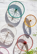 Decorated Colorful Bicycle Wheels Hung On A White Wall
