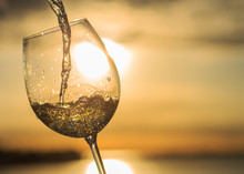Female Hand With A Glass Of White Wine On The Background Of A Beautiful Sunset.  Travel Vacations Concept.