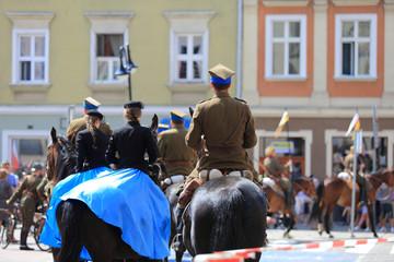 Kobiety w niebieskich sukniach i Żołnierze Wojska Polskiego na koniach.