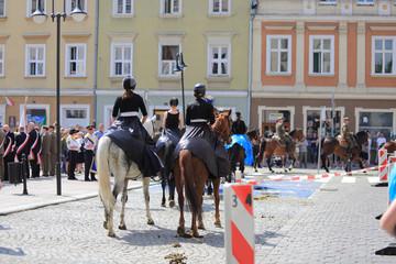 Kobiety w czarnych długich spudnicach i Żołnierze Wojska Polskiego na koniach.