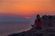 Meditation on the beach. A woman sits on a cliff above the ocean and does yoga. Femininity. Force. Soft shades at sunset. Beautiful scenery. Amazing sunset on the sea. Cloudy sky.Magic of nature.