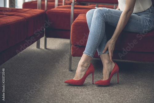 Tablou Canvas Close up female hand keeping leg while wearing high heel shoes