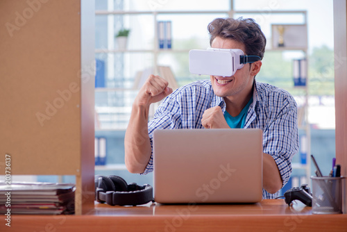 Fototapety, obrazy: Young man playing computer game with virtual reality glasses