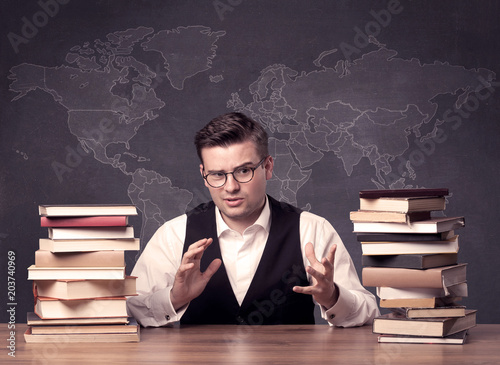 A young ambitious geography teacher in glasses sitting at classroom a young ambitious geography teacher in glasses sitting at classroom desk with pile of books in gumiabroncs Image collections