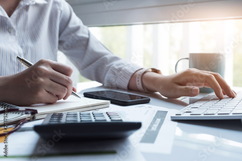 Business women using computer and calculator during note some data on notepad fo Canvas Print