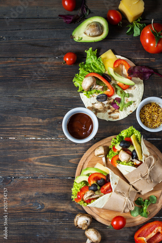 Healthy vegan lunch snack. Tortilla wraps with mushrooms, fresh vegetables and Ingredients on wooden background.