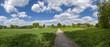 Feldweg mit landwirtschaftlich genutzter Ackerfläche und Streuobstwiese bei schönem Wetter