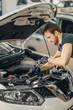 mechanic working in car hood in garage