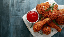Fried Crispy Chicken Legs, Thigh On White Cutting Board With Ketchup And Herbs