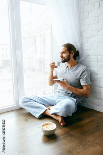 Morning Coffee. Man Enjoying Hot Drink Near Window Poster