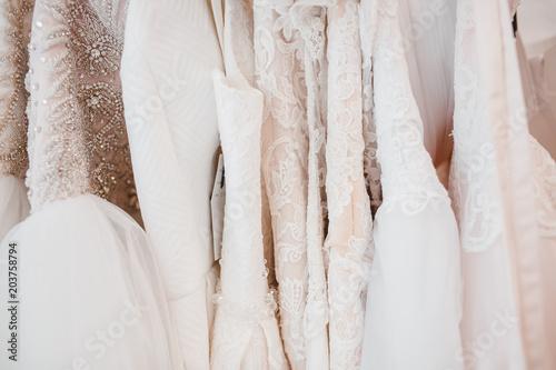 Fotografija White modern wedding dresses in gown store.