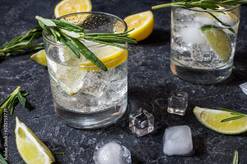 Keuken foto achterwand Cocktail Alcoholic drink gin tonic cocktail with lemon, rosemary and ice on stone table
