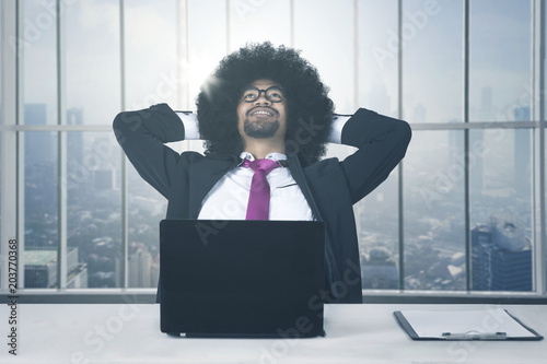 Fotografie, Obraz  African american with laptop relaxing at office