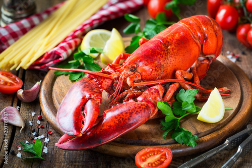 Foto Steamed red lobster on a wooden cutting board with parsley, lemon wedges and spaghetti at the background