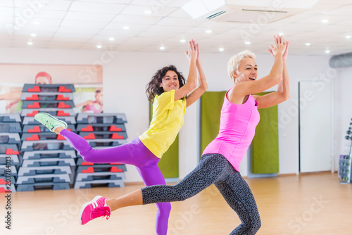Fotografie, Obraz  Happy female athletes doing aerobics exercises or Zumba dance workout to lose we