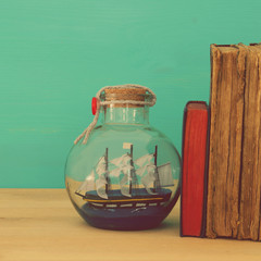 nautical concept image with sail boat in the bottle next to old books over wooden table. Selective focus.