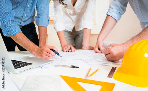 Civil engineers in discussion of construction plans for building in architect office