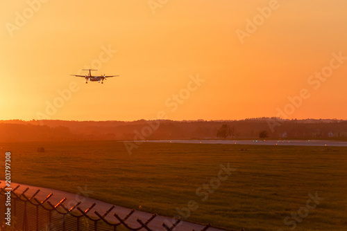 Fotografia, Obraz  Passenger plane approaching at Lech Walesa Airport in Gdansk at sunset time