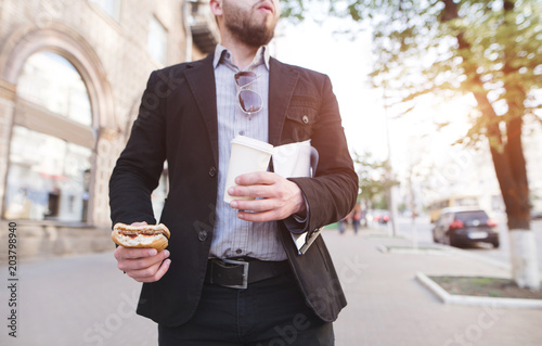 Fotografía  A businessman walking down the street with a snack and coffee in his hands