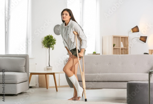 Leinwand Poster Young woman with crutch and broken leg in cast at home
