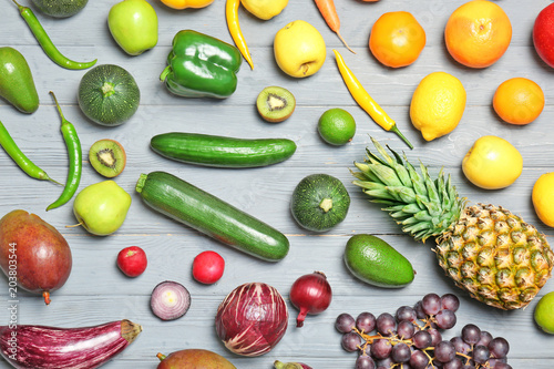 Fotografía  Rainbow collection of ripe fruits and vegetables on grey background, top view