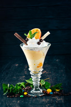 Ice Cream With Oranges. On A Black Wooden Background. Copy Space.