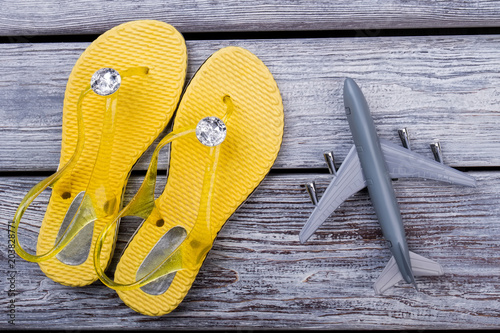Flip flops and toy airplane, flat lay. Dark wooden surface background.