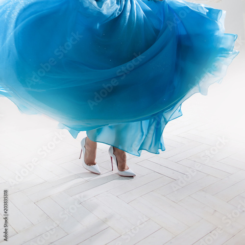 Stylish woman's feet in a puffy skirt and white shoes. Wall mural