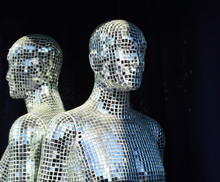 Male Mannequin Covered With Slices Of A Mirror On A Black Background