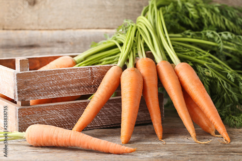 Fresh and ripe carrots in crate on wooden table Canvas Print