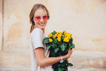 Smiling Charming Woman In Sunglasses Holds A Bouquet Of Yellow Roses, Looking At Camera. Outdoors.
