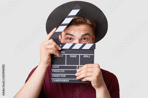 Photo Professional male actor ready for shooting film, holds movie clapper, prepares for new scene, wears special clothes, isolated on white background
