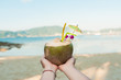 Woman s hand holding coconut cocktail