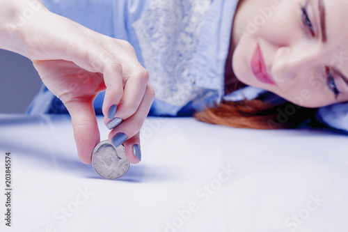 Woman spinning a coin to make decision  Heads or tails game