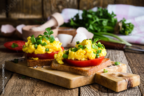 Scrambled eggs on two pieces of toast with green onion and tomatoes