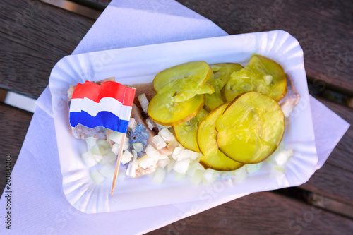 Deurstickers Amsterdam Fresh herring with onion, pickled cucumber pieces and Netherlands flag close up. Traditional Amsterdam street food.