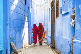 Fototapeta Uliczki - Two women dressed in the traditional Indian Saree are walking through the narrow streets of the blue city of Jodhpur, Rajasthan, India.