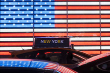 Some Cars And A Taxi Are Lined Up In Times Square Under An Illuminated American Flag. Manhattan, New York City, USA.
