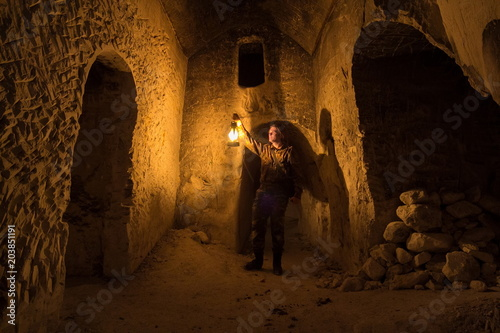 Man with kerosene lamp explores ancient abandoned underground chalky cave temple Wallpaper Mural