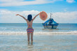 slim woman in bikini holding hat and hand up in the air cheerfully the sea beach enjoyment, with local ferry boat in background