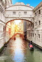 Beautiful View Of The Bridge Of Sighs In Venice With Rays Of Sunlight, And Venetian Gondola On Green Canal, Venice, Italy.