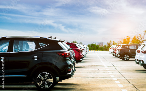 Luxury black, white and red new suv car parked on concrete parking area at factory with blue sky and clouds. Car stock for sale. Car factory parking lot. Automotive Industry concept. Car dealership.