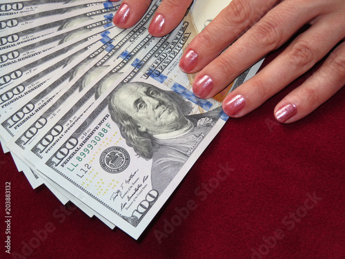 US dollars and female hands on a background of table covered by red fabric Poster