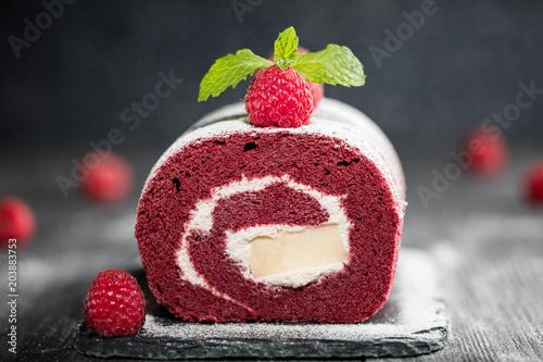 Fotografie, Obraz  Sponge Swiss roll cake  with fresh raspberry and sugar icing on dark background