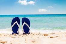 Pair Of Flip Flops On Sand Beach With Tropical Blue Sea And Sky In Background In Summer